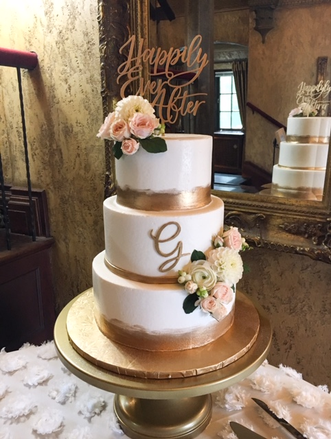 Three tiered cake with gold accents and fresh flowers